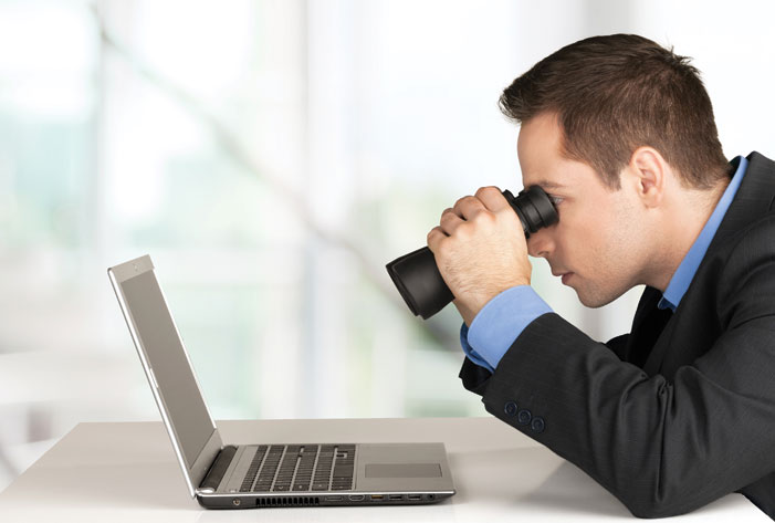 Business man looking at a screen with binoculars